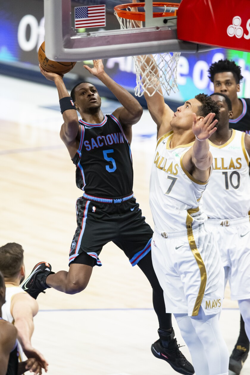 El escolta de los Kings de Sacramento De'Aaron Fox intenta un disparo ante la defensa del alero de los Mavericks de Dallas Dwight Powell en la segunda mitad del encuentro del domingo 18 de abril de 2021, en Dallas. (AP Foto/Brandon Wade)