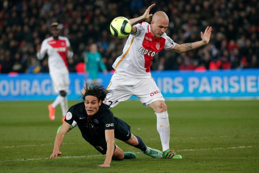 PSG's Edinson Cavani, left, challenges for the ball with Monaco's Andrea Raggi, during their French League One soccer match, at the Parc des Princes stadium, in Paris, Sunday, March 20, 2016. (AP Photo/Thibault Camus)
