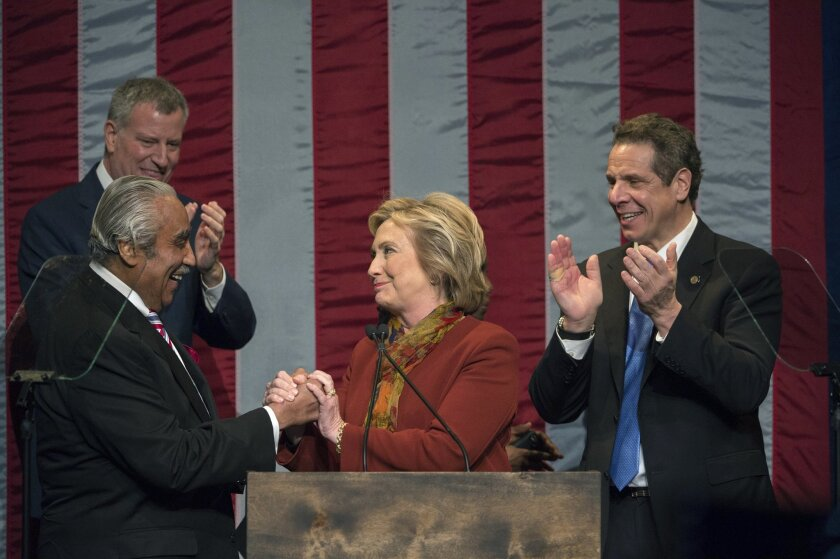 New York Mayor Bill de Blasio, left and Gov. Andrew Cuomo, right watch as Democratic presidential candidate Hillary Clinton, center shakes hands with Rep. Charles Rangel, R-N.Y., left, as she takes the stage to speak at the Schomburg Center for Research in Black Culture, Tuesday, Feb. 16, 2016, in