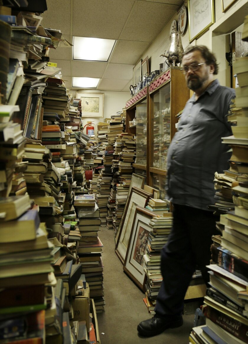 In this photo taken Monday, Feb. 8, 2016 Jonathan Klass, walks out of his office in his bookstore containing some 2 million books and prints in Johannesburg, South Africa. The Collectors Treasury, a three-storey bookshop owned by brothers Jonathan and Geoff Klass, is dedicated to preserving history