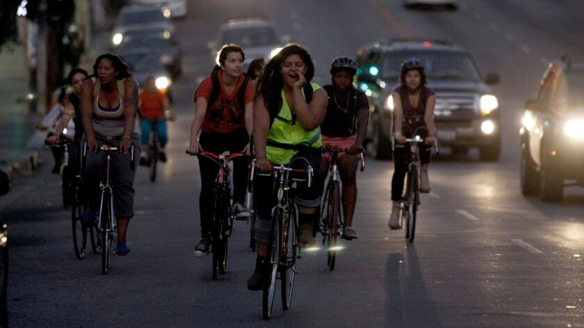 Evelyn Martinez (front/green vest), shouts instructions as she, along with other female riders and some members of the Ovarian Psycos, ride through the Boyle Heights area of Los Angeles.