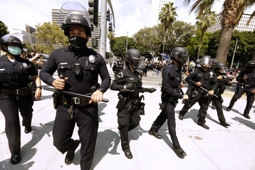 A row of LAPD officers in riot helmets and wielding batons