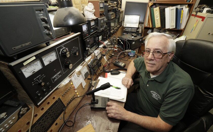 "In this Friday, March 13, 2020 photo, Paul Buescher poses by his ham radio, in Northfield Center Township, Ohio. Buescher is one of 32 members of a group in northeastern Ohio that shares a farm packed with enough canned and dehydrated food and water to last for years. For those in the often-mocked ""prepper"" community, this is quickly becoming their ""I told you so"" moment, as panic buying has cleared store shelves across the U.S. amid growing fears that the new coronavirus will force many Americans to self-quarantine for weeks in their homes. (AP Photo/Tony Dejak)"