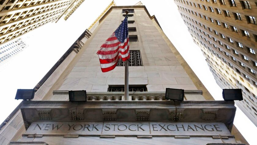 An American flag flies above the Wall Street entrance to the New York Stock Exchange.
