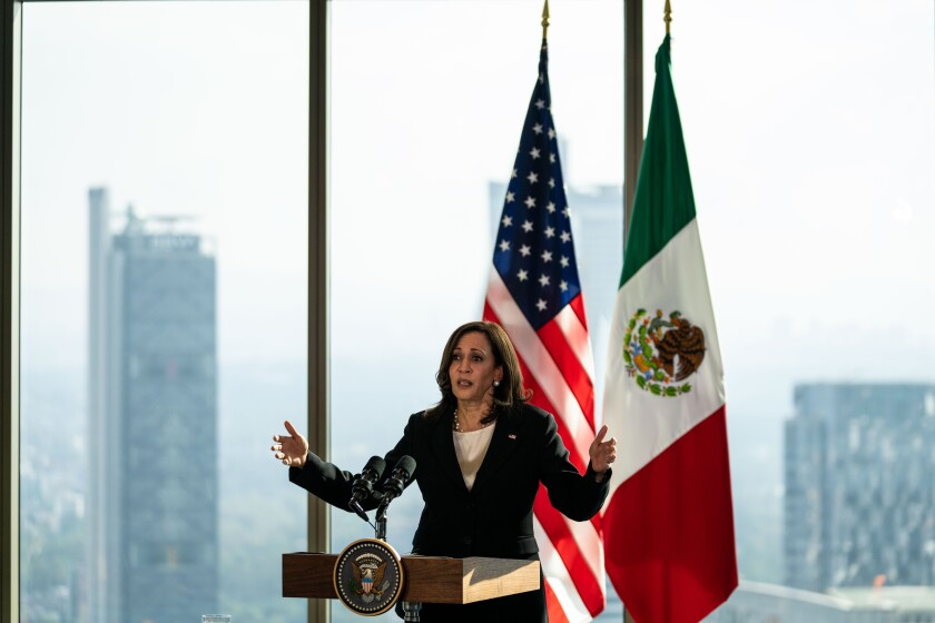 Kamala Harris gestures at a lectern in front of U.S. and Mexican flags.