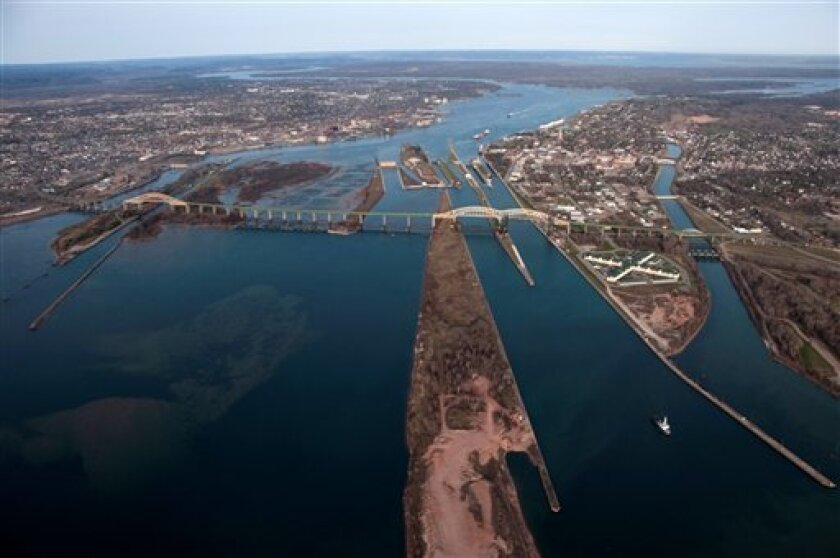This undated aerial photo provided Jan. 26, 2012, by the U.S. Army Corps of Engineers shows a view looking southward of the International Bridge crossing the St. Marys' River, connecting Sault Ste. Marie, Mich., right, and Sault Ste. Marie, Ontario, left, city of the same name. Hydroelectric dams and a series of gates near the bridge control water flows southwasrd from nearby Lake Superior through the river toward Lake Huron. Scientists are studying whether to change policies on releasing the water because of a debate over Great Lakes levels. (AP Photo/U.S. Army Corps of Engineers, Richard MacDonald)