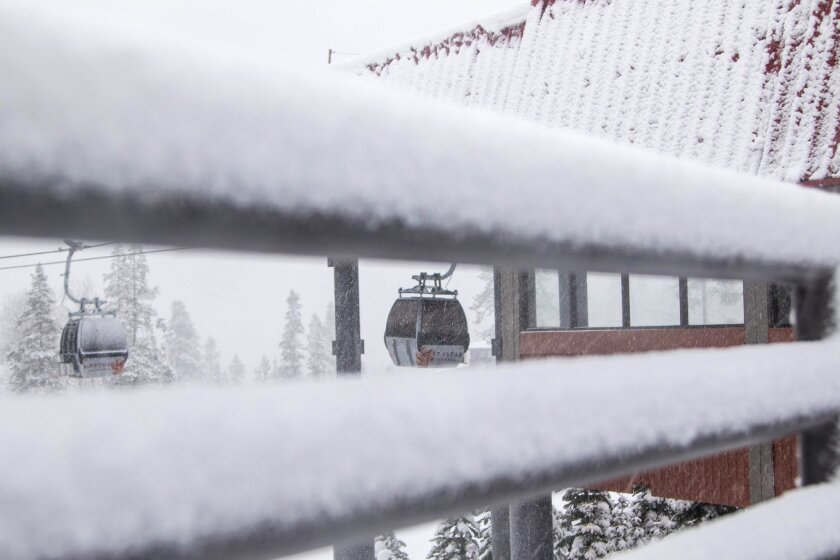 Framed by snow on a railing, gondolas deliver skiers and snowboarders to mid-mountain at Northstar California Resort in Truckee following a December snow storm.