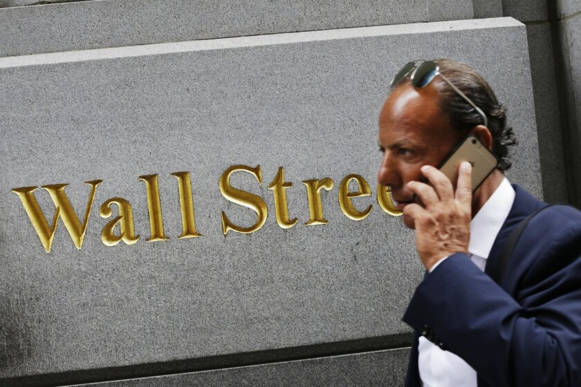 FILE - In this Monday, July 6, 2015, file photo, a man uses a mobile phone while walking by a building in the Financial District in New York. Global stock markets rose Wednesday, July 29, 2015, as Chinese shares rebounded after a record sell-off and attention turned to a Federal Reserve meeting that might give clues about the timing of a U.S. interest rate hike. (AP Photo/Mark Lennihan, File)