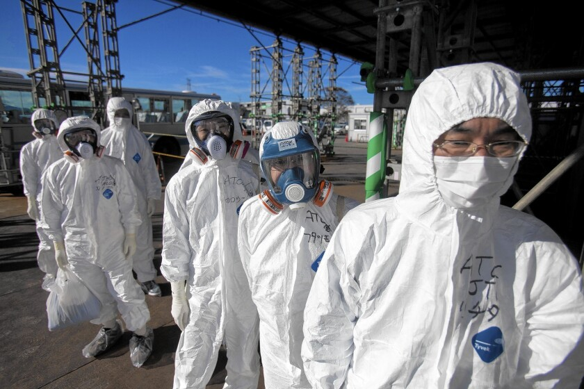 Workers in protective suits and masks wait to enter the emergency operation center at the crippled Fukushima Dai-ichi nuclear power station in Okuma, Japan, on Nov. 12, 2011.