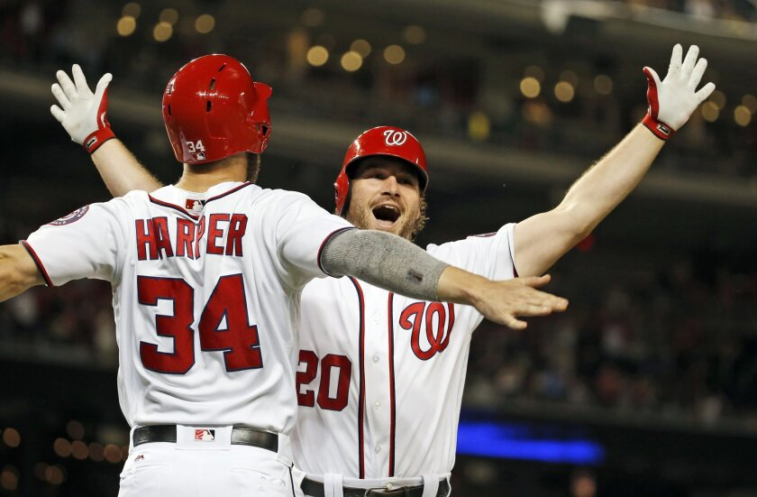 Washington Nationals' Bryce Harper (34) celebrates with Daniel Murphy (20) after Murphy's two-run home run during the eighth inning of a baseball game against the New York Mets at Nationals Park, Wednesday, June 29, 2016, in Washington. The Nationals won 4-2. (AP Photo/Alex Brandon)