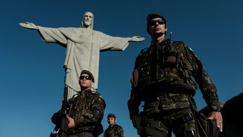 Brazlian army personnel patrol in front of the statue of Christ the Redeemer atop Corcovado Hill in Rio de Janeiro
