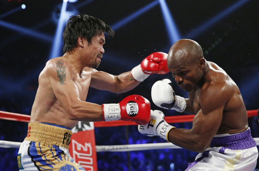 Manny Pacquiao, left, and Timothy Bradley trade punches in the middle of the MGM Grand Garden Arena ring during their WBO welterweight title fight on April 9.