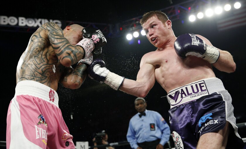 """Saul """"Canelo"""" Alvarez, right, attempts an uppercut on Miguel Cotto during their WBC middleweight title bout on Nov. 21 in Las Vegas."""