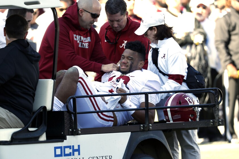 Alabama quarterback Tua Tagovailoa is carted off the field after suffering a season-ending hip injury against Mississippi State on Saturday.