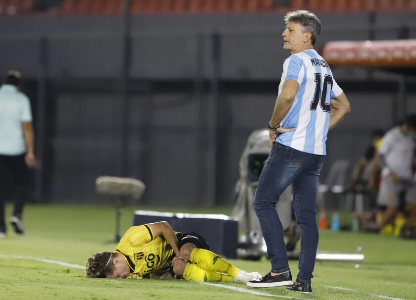 Portando la camiseta de Diego Maradona, el técnico de Gremio Renato Gaucho camina junto a Bautista Merlini, del Guaraní de Paraguay, quien fue derribado durante el partido de la Copa Libertadores disputado el jueves 26 de noviembre de 2020 (Nathalia Aguilar/Pool via AP)