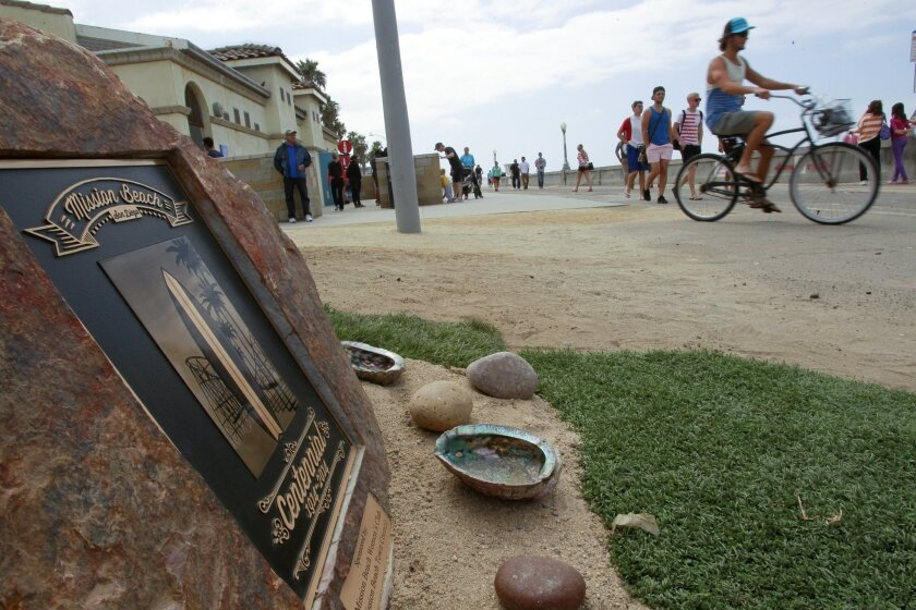 People ride bikes and walk past the Mission Beach Centennial monument after it was unveiled.