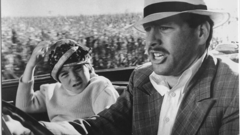 1973: American actor Ryan O'Neal drives a car while his daughter, American actor Tatum O'Neal, holds
