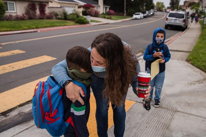 Andrea Morales abraza a su hijo Reece mientras su hijo Keiran se encuentra cerca