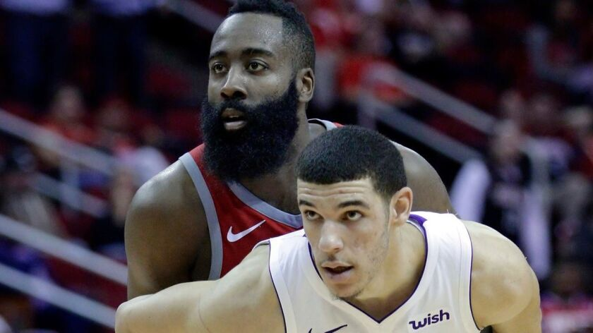 Houston Rockets guard James Harden (13) and Lakers guard Lonzo Ball (2) hold each other in the second half on Wednesday.