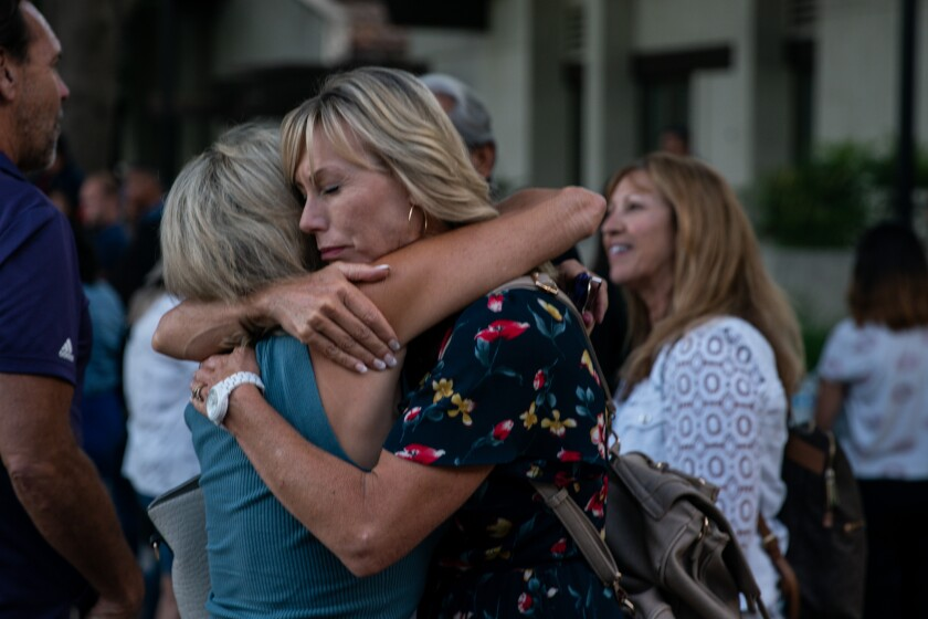 GILROY, CALIF. - JULY 29: Kelly Ramirez, of Gilroy gives a hug, after a candlelight vigil at Gilroy City Hall on Monday, July 29, 2019 in Gilroy, Calif. (Kent Nishimura / Los Angeles Times)