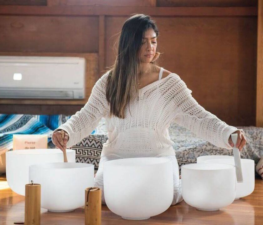 Natalie Valle, from Love & Alchemy, with the crystal quartz singing bowls she plays during the sound baths she leads at Surya.
