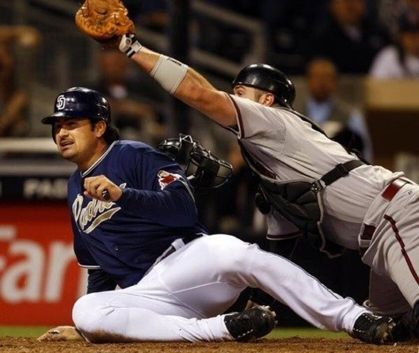 Adrian Gonzalez is safe at home, beating the throw to Arizona catcher Chris Snyder after a two-run single by Brian Giles in the Padres' six-run sixth inning.