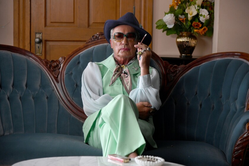 Udo Kier holds a cigarette while wearing a mint green pantsuit, sunglasses and a fedora with his legs crossed at the knee.