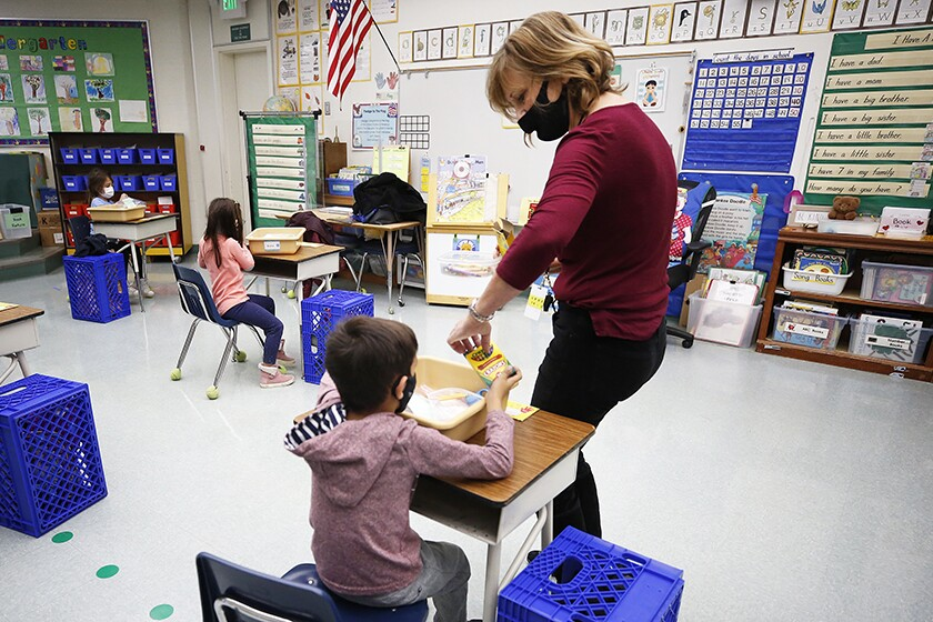 A teacher, wearing a mask, collects crayons from a student at his desk.
