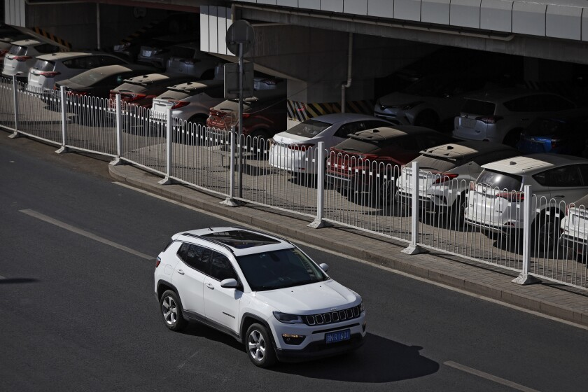 FILE - In this March 14, 2019, file photo, an SUV moves past dust-covered new Toyota cars stored underneath an overpass in Beijing. China's auto sales sank 5.4% in November from a year ago, putting the industry's biggest global market on track to shrink for a second year, an industry group reported Tues, Dec. 10, 2019. Drivers bought just over 2 million SUVs, sedans and minivans, according to the China Association of Automobile Manufacturers.(AP Photo/Andy Wong, File)