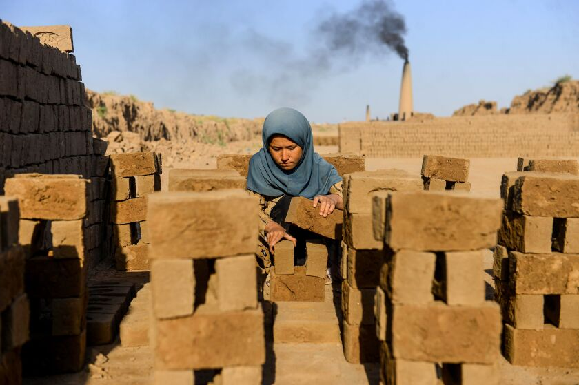 A young girl collects bricks as she works as a laborer at a brick factory on the outskirts of Herat on August 26, 2020.