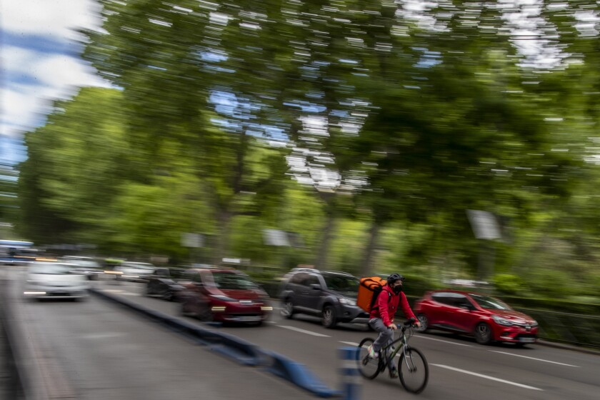 A delivery worker rides his bike in Madrid, Spain, Tuesday, May 11, 2021.