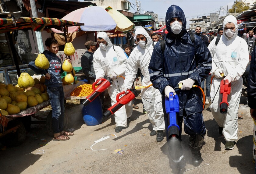 Workers wearing protective gear spray disinfectant at the main market in Gaza City on Thursday.