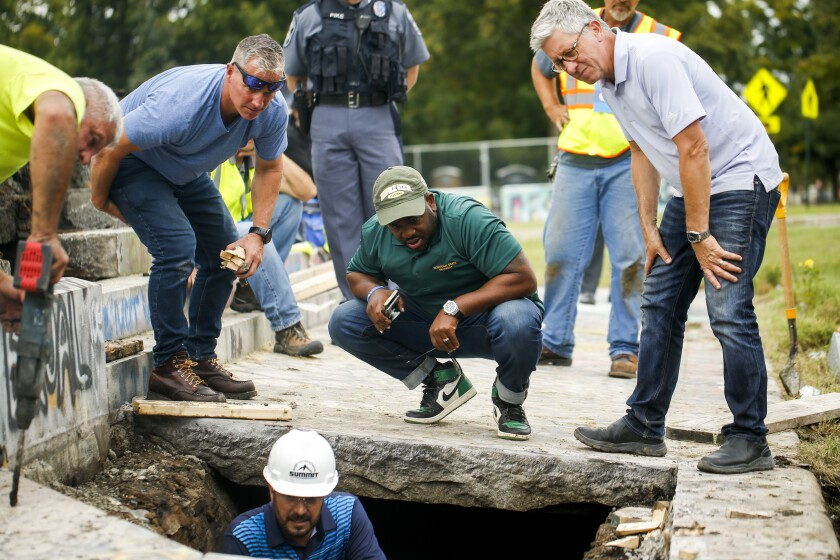 Devon Henry, owner of the construction company that removed the Confederate Gen. Robert E. Lee statue, center, looks on as crews work on retrieving a 134-year-old time capsule at Monument Avenue, Thursday, Sept. 9, 2021, in Richmond, Va. The time capsule will be replaced with a new one. (Shaban Athuman/Richmond Times-Dispatch via AP)
