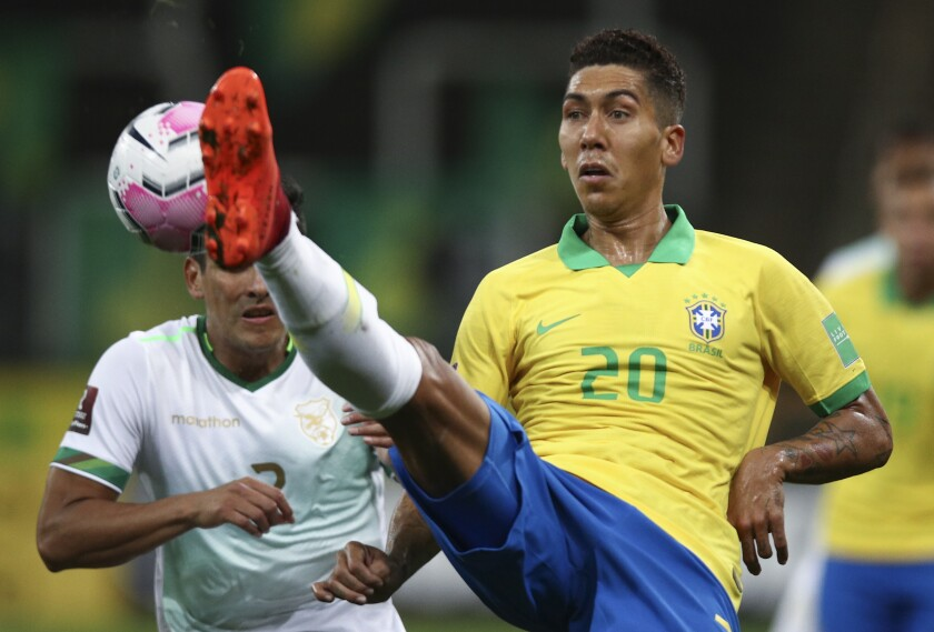 Brazil's Roberto Firmino, right, fights for the ball with Bolivia's Gabriel Valverde during a qualifying soccer match for the FIFA World Cup Qatar 2022 at the Neo Quimica arena in Sao Paulo, Brazil, Friday, Oct. 9, 2020. (Buda Mendes/Pool via AP)