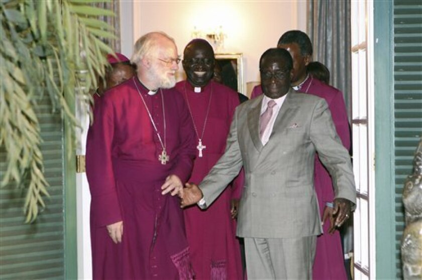 The Archbishop of Canterbury Rowan Williams, left, meets with Zimbabwe's President Robert Mugabe at the State House in Harare, Zimbabwe, Monday, Oct. 10, 2011. The Anglican Church in Zimbabwe has been divided since breakaway Bishop Nolbert Kunonga's excommunication in 2007. He has taken over the main cathedral, schools and the church's bank accounts. The Archbishop and Mugabe are expected to discuss an end to the disruptions. (AP Photo/Tsvangirayi Mukwazhi)
