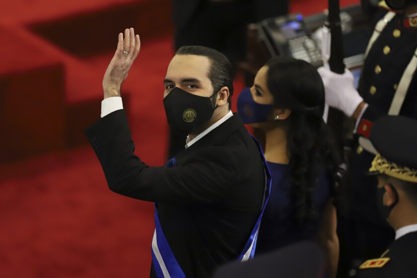 FILE - In this June 1, 2021 file photo, El Salvador's President Nayib Bukele waves during his annual address to the nation to congress, in San Salvador, El Salvador. Bukele's presidency so far is the story of one of Latin America's newest populist autocracies in the making: spending big to hand out goodies, branding opponents as enemies, raising the profile of the military. (AP Photo/Salvador Melendez, File)