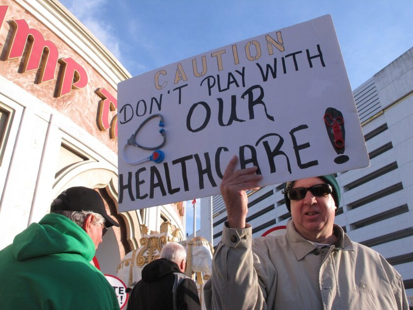 A union member holds a sign critical of billionaire investor Carl Icahn during a demonstration outside the Trump Taj Mahal casino in Atlantic City, N.J. on Wednesday March 23, 2016 to protest Icahn's refusal to reinstate health insurance and pension benefits that previous owners eliminated in bankruptcy court before Icahn acquired the casino last month. Icahn, the billionaire investor, accuses Local 54 of the Unite-HERE union, of trying to force the Taj Mahal to close by saddling it with unaffordable financial demands. (AP Photo/Wayne Parry)