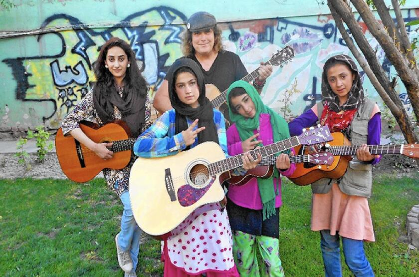 Rock musician and Cypress High alum Lanny Cordola and some of the children he taught to play guitar in Kabul, Afghanistan.