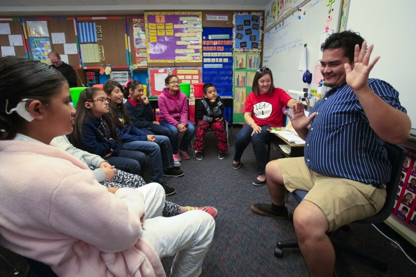 "Armando Bravo (right) uses American Sign Language to interpret the Dr. Seuss book, ""I Wish That I Had Duck Feet"" to Keri Gravette's classroom of students at Davila Day School, which serves deaf and hearing-impaired children."