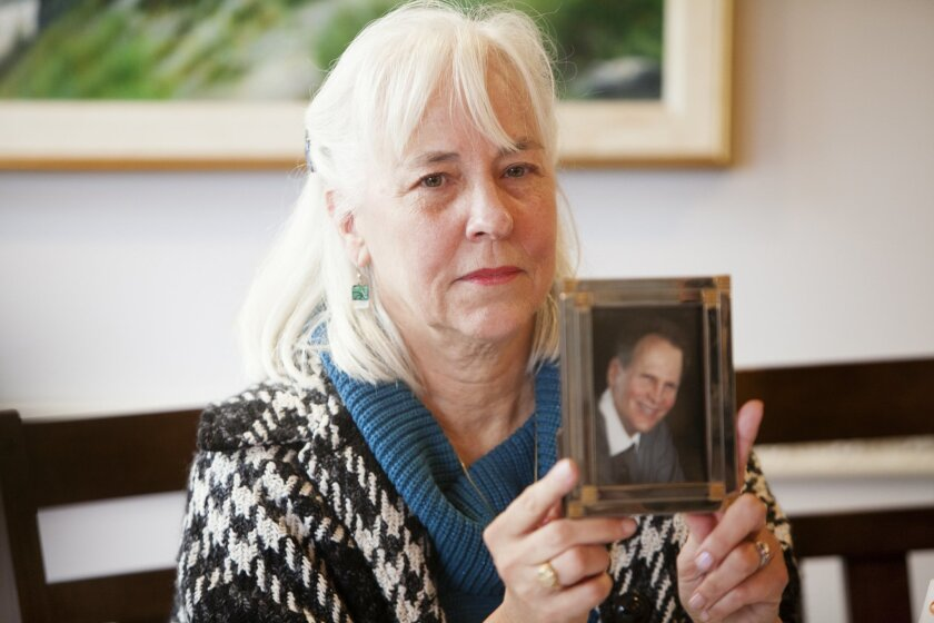 Rebecca Brown holds a picture of her husband, retired SDPD criminalist Kevin Brown, who was investigated as a suspect in the 1984 murder of Claire Hough. He committed suicide during the investigation, and his widow has filed a wrongful death claim against San Diego police.