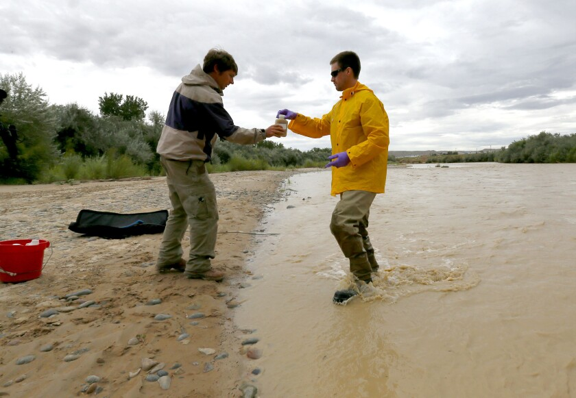 Ben Brown with the Utah Department of Environmental Quality, left, receives a San Juan River sample from hydrologic technician Ryan Parker in Montezuma Creek, Utah.