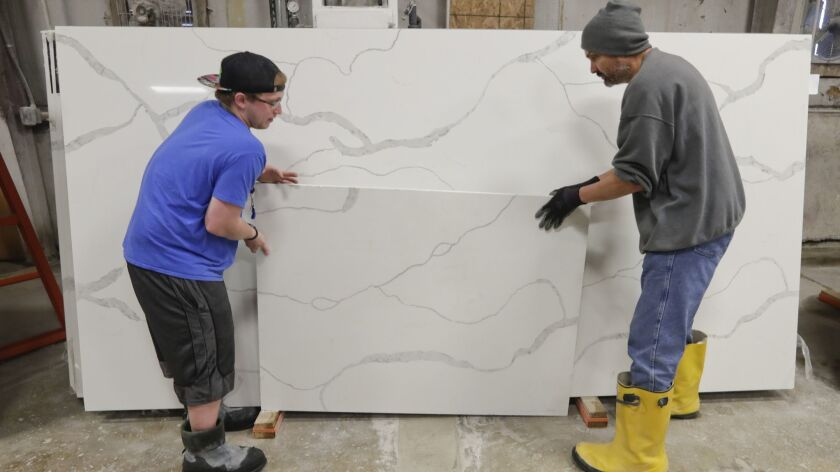 Workers move imported quartz slabs from China in the warehouse at Marble Uniques in Tipton, Ind., on