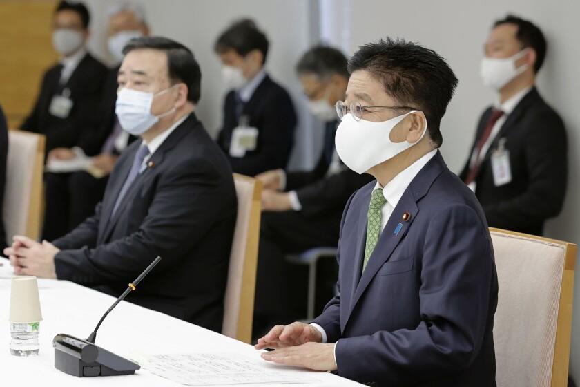 El secretario jefe del gabinete japonés, Katsunobu Kato (derecha), asiste a una reunión con el gobernador de la prefectura de Aomori, sede de la planta de reprocesamiento de combustible nuclear, en Tokio, el miércoles 21 de octubre de 2020. (Kyodo News vía AP)
