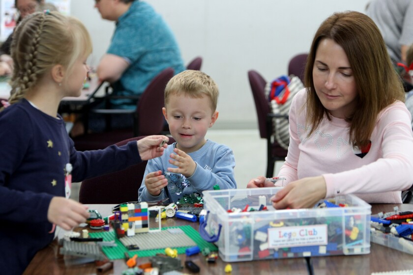 Natalia Kulikova (right) and her children Kseniia (left), 8, and Andrei, 3, play with LEGOs at a library's LEGO Club on March 7, 2020; before public libraries were closed due to coronavirus (COVID-19) concerns, Experts recommend parents have kids do stimulating, hands-on activities at home and have a daily routines during school closures.