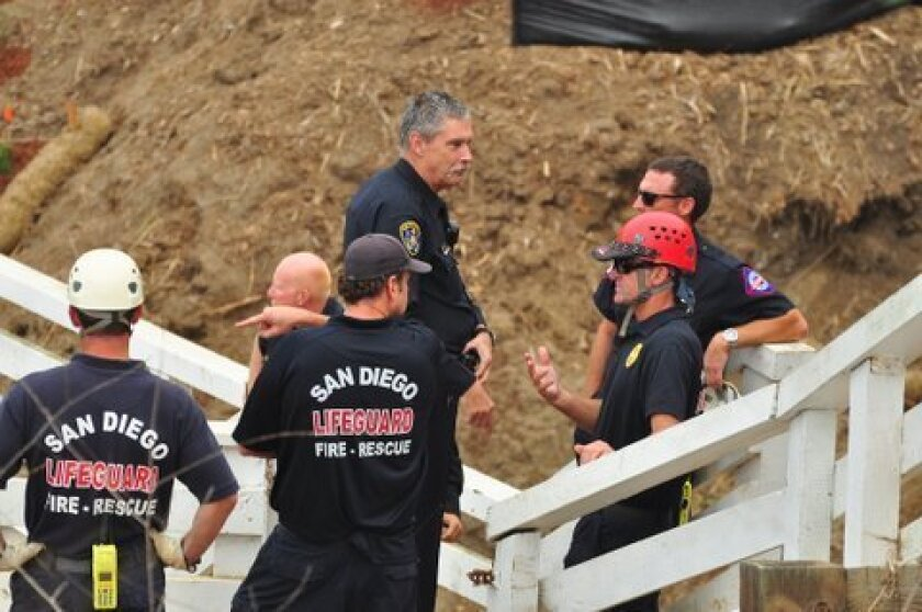 Lifeguards and other responders discuss the kayak accident. Photo: Greg Wiest