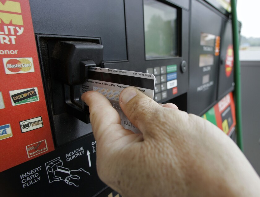 A customer swipes a credit card at a gas station pump.