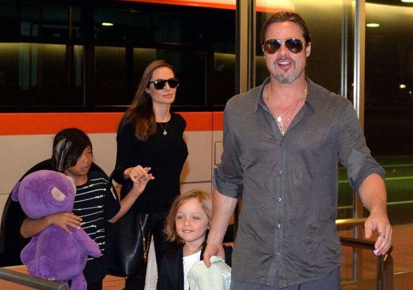 Brad Pitt (der.) al lado de algunos de sus hijos; al fondo aparece Angelina Jolie. El actor está siendo acusado de abusar de uno de estos niños.