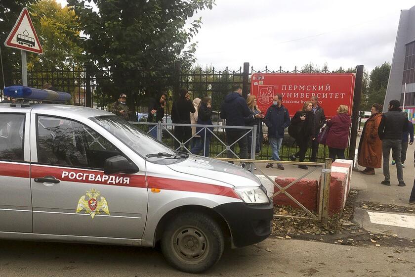 Gente tras una cerca cerca de la Universidad Estatal de Perm, con la Posguardia (Guardia Nacional) rusa