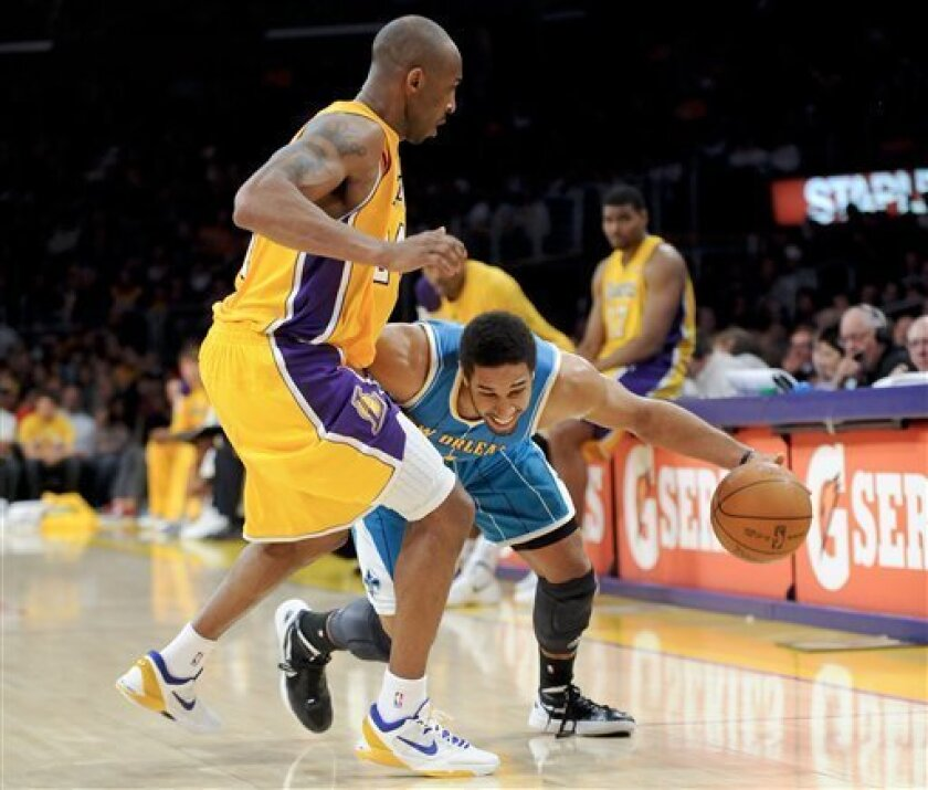 New Orleans Hornets guard Xavier Henry, right, attempts to bet by Los Angeles Lakers guard Kobe Bryant, left, in the first half of an NBA basketball game on Saturday, March 31, 2012, in Los Angeles. (AP Photo/Gus Ruelas)