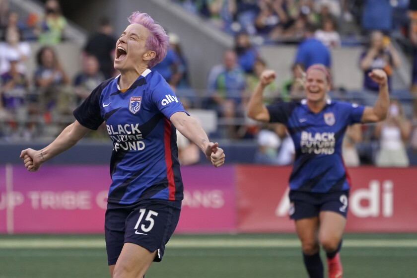 OL Reign forward Megan Rapinoe, left, celebrates with Eugenie Le Sommer, right, after scoring a goal on a penalty kick against the Portland Thorns during the first half of an NWSL soccer match, Sunday, Aug. 29, 2021, in Seattle. The goal was Rapinoe's second during the first half. (AP Photo/Ted S. Warren)